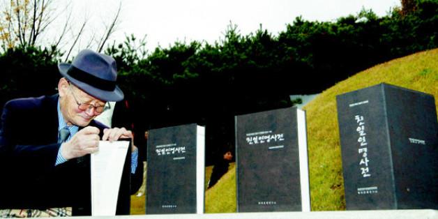 지난 2009년 11월 8일 서울 용산구 효창동 백범 김구 묘소에서 열린 '친일인명사전 발간 국민보고대회'에서 한 시민이 백범의 제단에 바쳐진 사전을 살펴보고 있다.