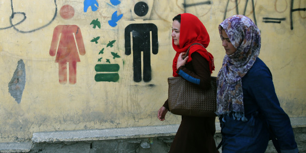 In this Tuesday, March 31, 2015 photo, Afghan university students walk past graffiti, in Kabul, Afghanistan. Farkhunda, a 27-year-old religious scholar, was beaten to death by a frenzied mob on March 19 after an argument with a peddler at Kabul's Shah-Do Shamshira mosque. Poets, musicians, actors and activists gathered this week to commemorate the short life and violent death of a woman who has become a symbol for justice and women's rights in a country that historically elevates warlords and battlefield heroes to national icons. (AP Photo/Massoud Hossaini)