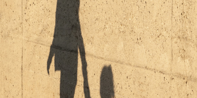 A Child being lead away by a women. there shadows reflected on a wall.