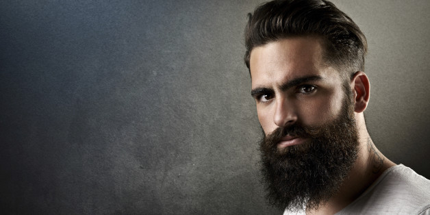Portrait of a brutal bearded man with tattoos