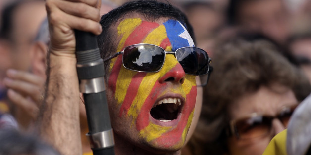 A supporter of the independence of the Catalonia region of Spain, with an estelada or pro independence flag painted on his face gathers in Catalonia square during a rally in Barcelona, Spain, Sunday, Oct. 19, 2014. Thousands of demonstrators crowded a central square in Barcelona during the main campaign event organized by two major pro independence civil society organizations ahead of the vote scheduled for Nov. 9th. Spain's wealthy Catalonia region calls off an independence vote but says an uno