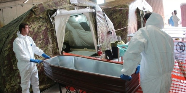 Des experts italiens s'apprêtent à autopsier des migrants dans une tente réfrigérée le 5 novembre 2015 à Melilli, en Sicile
