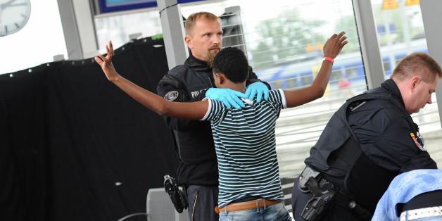 Ein junger Mann aus Eritrea wird am 02.09.2015 am Bahnhof in Rosenheim (Bayern) von einem Polizisten abgetastet. (Archivbild)