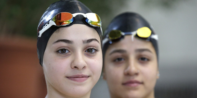 In this photo taken Monday, Nov. 9, 2015, Ysra Mardini, left, and her sister Sarah, right, from Syria pose for a photo during a training session in Berlin, Germany. Two months ago the sisters, who were once among Syria's brightest swimming stars, were swimming for their lives, after jumping off an inflatable boat that began taking on water carrying refugees to Greece. (AP Photo/Michael Sohn)