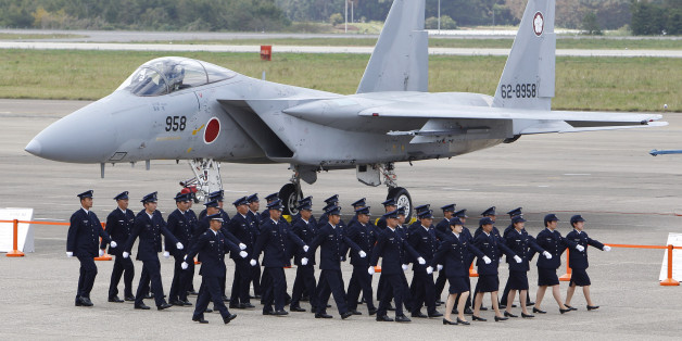 Japan Self-Defense Force (SDF) members walk in front of F-15 J/DJ Fighter during the annual Self-Defense Forces Commencement of Air Review at Hyakuri Air Base, north of Tokyo,  Sunday, Oct. 16, 2011. (AP Photo/Shizuo Kambayashi)
