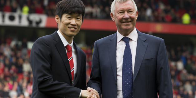 Manchester United former player Park Ji-sung, left, shakes hands with former manager Alex Ferguson as Park is introduced as a new ambassador for the club before the team's English Premier League soccer match against  Everton at Old Trafford Stadium, Manchester, England, Sunday Oct. 5, 2014. (AP Photo/Jon Super)