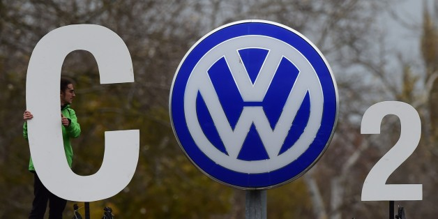An activist of environmental organisation Greenpeace holds a giant letter to display 'CO2' around the logo of German car maker Volkswagen ( VW ) at the entrance of the company's headquarters in Wolfsburg, on November 9, 2015. VW is engulfed in a massive pollution scandal that has so far centred on so-called defeat devices, sophisticated software fitted into diesel engines to skew the results of tests for nitrogen oxide emissions. The embattled auto giant said an internal probe had uncovered 'inc