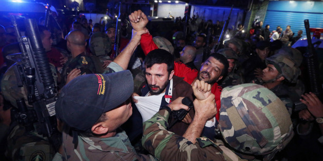 Lebanese soldiers arrest a suspected attacker attacker near the scene of a twin suicide attack in Burj al-Barajneh, southern Beirut, Lebanon, Thursday, Nov. 12, 2015 that struck a Shiite suburb killed and wounded dozens, according to a Lebanese official. (AP Photo/Bilal Hussein)