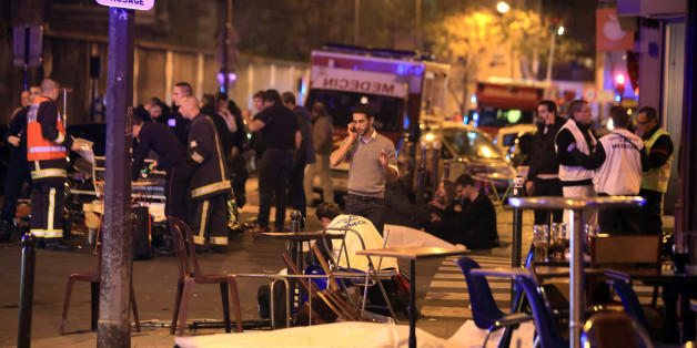 Victims lay on the pavement in a Paris restaurant, Friday, Nov. 13, 2015.  Well over 100 people were killed in Paris on Friday night in a series of shooting, explosions. French President Francois Hollande declared a state of emergency and announced that he was closing the country's borders. (AP Photo/Thibault Camus)
