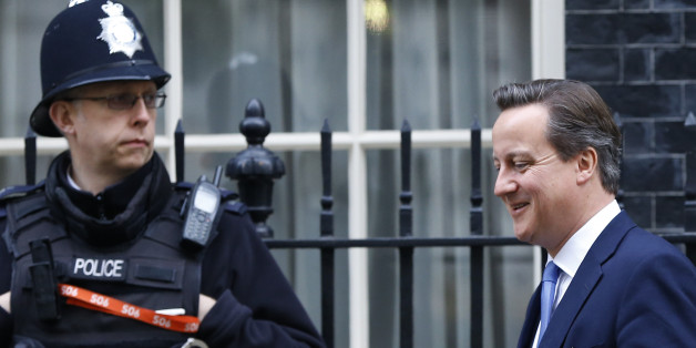 A police officer stands by as Britain's Prime Minister David Cameron leaves 10 Downing Street in London, Thursday, Nov. 20, 2014. David Cameron will attend a Liaison Committee Thursday, the meeting focuses on the Governance of the UK in the light of the Scottish Referendum. (AP Photo/Kirsty Wigglesworth)