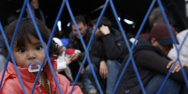 A migrant girl looks through the fence waiting to board a train at the train station in Sid, about 100 km west from Belgrade, Serbia, Wednesday, Nov. 11, 2015. Slovenia on Wednesday began erecting a razor-wire fence along its border with Croatia to control the influx of migrants, as European and African leaders gathered in Malta to seek long-term solutions to the flow of people making their way across Europe. (AP Photo/Darko Vojinovic)