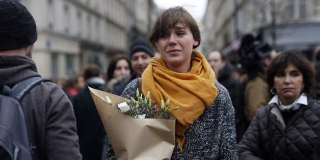 A woman carrying flowers cries in front of the Carillon cafe and the Petit Cambodge restaurant in Paris Saturday Nov. 14, 2015, a day after over 120 people were killed in a series of attacks in Paris. French President Francois Hollande said at least 127 people died Friday night when at least eight attackers launched gun attacks at Paris cafes, detonated suicide bombs near France's national stadium and killed hostages inside a concert hall during a rock show. (AP Photo/Jerome Delay)