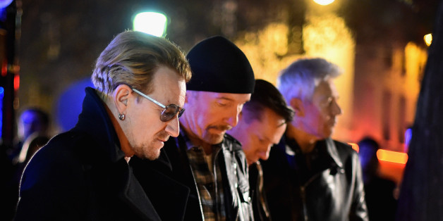 PARIS, FRANCE - NOVEMBER 14:  Bono and band members of U2 pay their respects and place flowers on the pavement near the scene of yesterday's Bataclan Theatre terrorist attack on November 14, 2015 in Paris, France. At least 120 people have been killed and over 200 injured, 80 of which seriously, following a series of terrorist attacks in the French capital.  (Photo by Jeff J Mitchell/Getty Images)