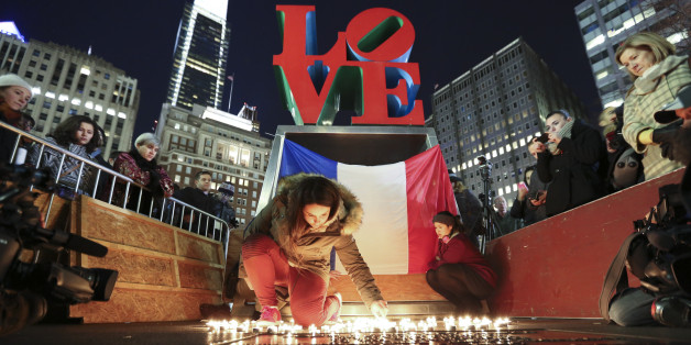 Cloe Tinchant lights candles in LOVE Park, Saturday, Nov. 14, 2015, during a candlelight vigil to remember the victims of the attacks in Paris. (AP Photo/Joseph Kaczmarek)