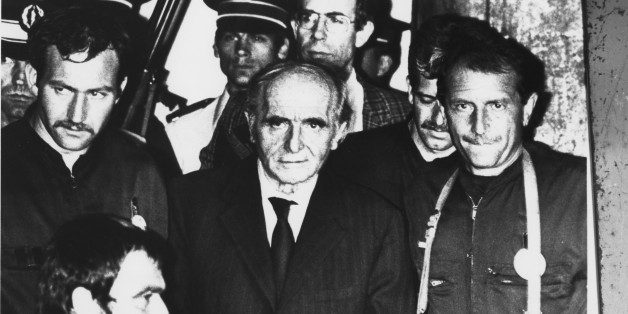 Lyon's, France, Gestapo chief during WW II, Klaus Barbie,  is pictured handcuffed as he is led out of the courtroom by heavily armed police officers after he was sentenced to life in prison July 4, 1987 in Lyon, France, for committed crimes against humanity. (AP Photo/Pool)