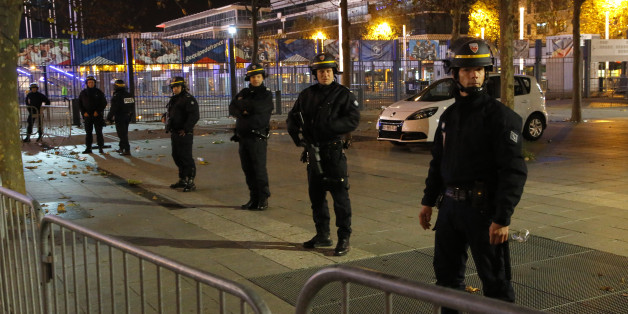Police officers secure the  Stade de France stadium during the international friendly soccer France against Germany, Friday, Nov. 13, 2015 in Saint Denis, outside Paris. Two police officials say at least 11 people have been killed in shootouts and other violence around Paris. Police have reported shootouts in at least two restaurants in Paris. At least two explosions have been heard near the Stade de France stadium, and French media is reporting of a hostage-taking in the capital. (AP Photo/Michel Euler)
