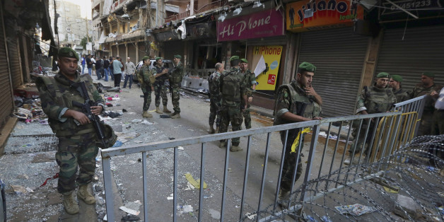 Lebanese army soldiers stand guard at the scene of Thursday's twin suicide bombings in Burj al-Barajneh, southern Beirut, Lebanon, Friday, Nov. 13, 2015. Schools and universities across Lebanon were shuttered Friday as the country mourned victims of twin suicide bombings that struck a crowded neighborhood south of the capital. (AP Photo/Bilal Hussein)