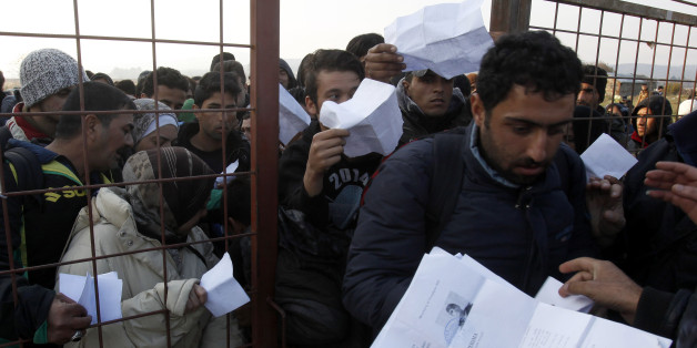 People hand in their documents for identification at the entrance of the transit center for refugees near the southern Macedonian town of Gevgelija, after crossing the border from Greece, Saturday, Nov. 14, 2015. Hundreds of thousands of migrants and refugees have passed the last few months through Macedonia as a part of the Balkan route, on their way to more prosperous European Union countries. (AP Photo/Boris Grdanoski)