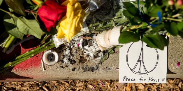 Mourners leave flowers and cards outside the gates of the French Embassy in Washington, Sunday, Nov. 15, 2015. The Islamic State group claimed responsibility for Friday's attacks on a stadium, a concert hall and Paris cafes that left more than 120 people dead and over 350 wounded.  (AP Photo/Andrew Harnik)
