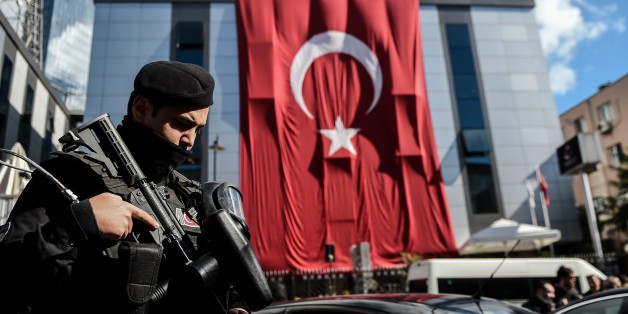 A Turkish riot policeman stands guard outside the headquarters of Bugun newspaper and Kanalturk television station in Istanbul during a protest against the Turkish government's crackdown on media outlets on October 28, 2015. Riot police firing tear gas and water cannon stormed the Istanbul headquarters of a media group linked to President Recep Tayyip Erdogan's bitter rival, on what was described as a dark day for democracy ahead of a pivotal election. The action triggered widespread concern about media freedom in Turkey, with critics accusing the government of trying to silence opponents of Erdogan's Justice and Development Party (AKP) before the November 1 legislative vote. AFP PHOTO / OZAN KOSE        (Photo credit should read OZAN KOSE/AFP/Getty Images)