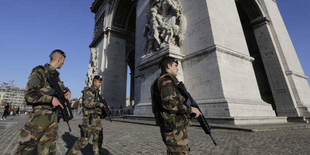 French soldiers patrol at the Arch of Triumph in the Champs Elysees district of Paris, France, Sunday, Nov. 15, 2015. Thousands of French troops deployed around Paris on Sunday and tourist sites stood shuttered in one of the most visited cities on Earth while investigators questioned the relatives of a suspected suicide bomber involved in the country's deadliest violence since World War II. (AP Photo/Amr Nabil)