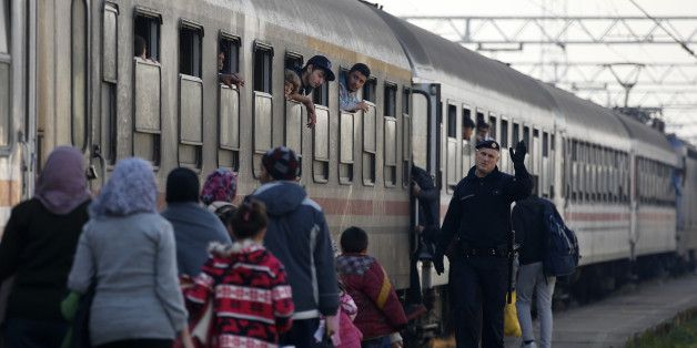 A Croatian police officer helps people board a train at the station in Sid, about 100 km west from Belgrade, Serbia, Tuesday Nov. 3, 2015. Serbia and Croatia have launched a direct train transfer of migrants from one country to another so asylum seekers no longer have to wait long hours outside in the cold. (AP Photo/Darko Vojinovic)