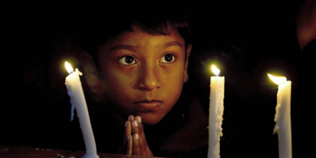 A Christian boy prays during a candlelight vigil for victims who were killed in Friday's attacks in Paris, at St. Thomas Church in Islamabad, Pakistan, Sunday, Nov. 15, 2015. Multiple attacks across Paris on Friday night have left scores dead and hundreds injured. (AP Photo/Anjum Naveed)