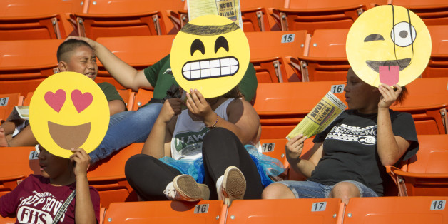 These Hawaii fans hold their emoji character mask in celebration of Halloween before the start of an NCAA college football game between Air Force and Hawaii, Saturday, Oct. 31, 2015, in Honolulu. (AP Photo/Eugene Tanner)