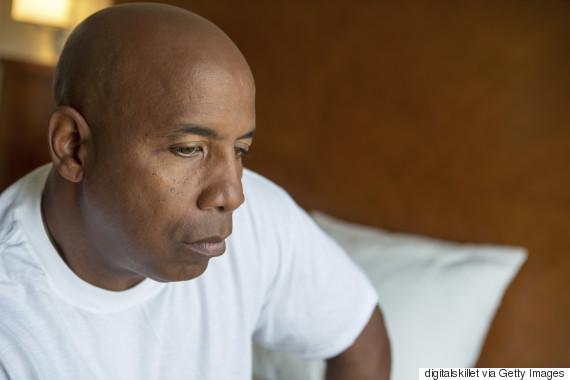 black man sad bed
