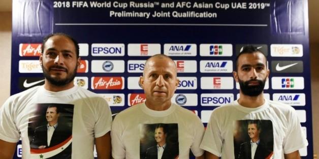Fajr Ibrahim (c), le sélectionneur de l'équipe de foot de Syrie, et le joueur Osama Omari (d) posent avec des T-shirts à l'effigie du président Bachar al-Assad en conférence de presse le 16 novembre 2015 à Singapour