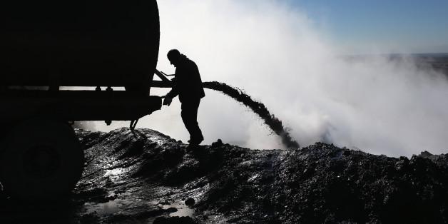 An worker unloads the dregs of oil refined into diesel fuel on November 14, 2015 near Derek, in Rojava, Syria.