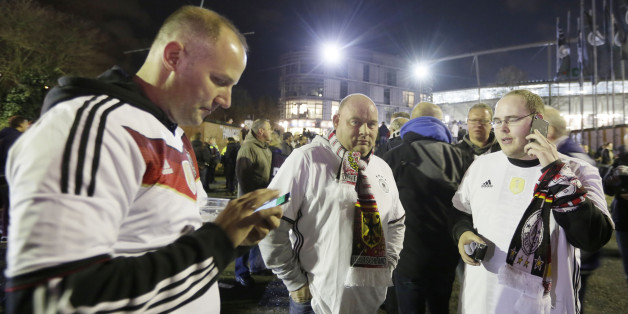 German soccer fans stand outside the stadium as the soccer friendly match between Germany and the Netherlands was cancelled in Hannover, Germany, Tuesday, Nov. 17, 2015. (AP Photo/Markus Schreiber)