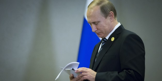 FILE - In this Monday, Nov. 16, 2015 file photo, Russian President Vladimir Putin reads his notes waiting for British Prime Minister David Cameron for their talks at the G-20 Summit in Antalya, Turkey. For President Vladimir Putin, the terror attacks in Paris marked a watershed moment in relations with the West. This week's summit in Turkey made it clear that the U.S. and its allies have warmed to the idea of closer ties with Russia, whose help they need to confront the challenge of the Isl