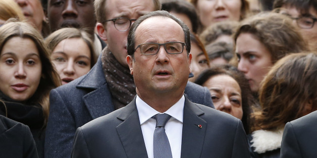 French President Francois Hollande stands among students during a minute of silence in the courtyard of the Sorbonne University in Paris, Monday, Nov. 16 2015. A minute of silence was observed throughout the country in memory of the victims of last Friday's attack. (Guillaume Horcajuelo, Pool via AP)
