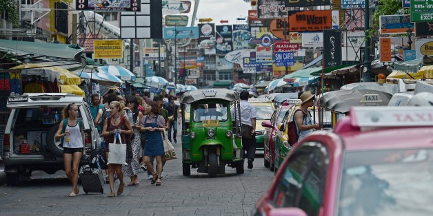 TO GO WITH Thailand-China-unrest-tourism-economy,FOCUS by Preeti JHATourists walk along Khao San road, popular with many foreign visitors, in Bangkok on August 21, 2015.  Busloads of visitors from China flocked to Bangkok's glittering Grand Palace on August 21 but, days after a bomb at another of the city's popular attractions killed five Chinese tourists, Thailand's biggest spending holidaymakers are rattled.      AFP PHOTO / Christophe ARCHAMBAULT        (Photo credit should read CHRISTOPHE AR