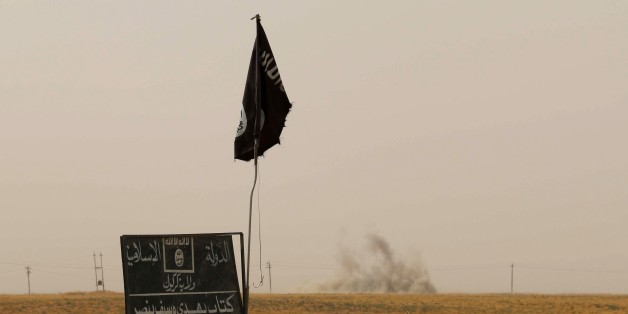Smoke rises in the distance behind an Islamic State (IS) group flag and banner after Iraqi Kurdish Peshmerga fighters reportedly captured several villages from IS group jihadists in the district of Daquq, south of the northern Iraqi multi-ethnic city of Kirkuk on September 11, 2015. An Iraqi officer said that the operation was launched in the morning with support from international coalition aircraft, and has succeeded in retaking ten villages from IS. AFP PHOTO / MARWAN IBRAHIM        (Photo credit should read MARWAN IBRAHIM/AFP/Getty Images)