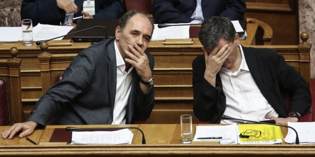 Greece's Finance Minister Euclid Tsakalotos, right, and Greek Economy Minister Giorgos Stathakis attend a committee meeting in the Parliament ahead of a full assembly debate and vote, expected around midnight , in Athens, Thursday, Aug. 13, 2015. The Greek government defended its new bailout program as tough but essential to avoid the nation's financial collapse, as it faced a rebellion in parliament ahead of a vote on the deal later in the day.(AP Photo/Yannis Liakos)