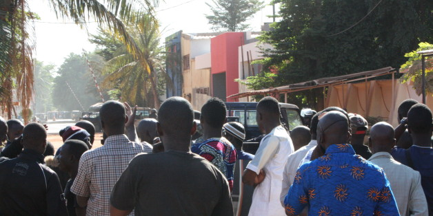 "Onlookers gather near the Radisson Blu hotel after gunmen stormed the building in Bamako, Mali, Friday, Nov. 20, 2015. Men shouting ""God is great"" and armed with guns and throwing grenades stormed into the Radisson Blu Hotel in Mali's capital Friday morning.(AP Photo/Harouna Traore)"