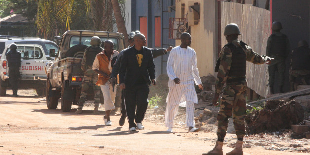 Security force personnel escort people fleeing from the Radisson Blu Hotel in Bamako, Mali, Friday, Nov. 20, 2015. The company that runs the Radisson Blu Hotel in Mali's capital says assailants have takenhostages in a brazen assault involving grenades. (AP Photo/Harouna Traore)