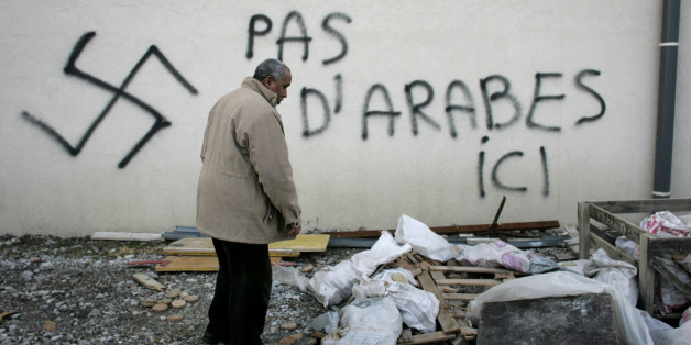 "A Muslim resident stands by racial slurs painted on the walls of a mosque in the town of Saint-Etienne, central France, Monday Feb.8, 2010. The French Council of the Muslim Faith says such vandalism has multiplied in France ""in a very worrisome way."" The council repeated a demand for the government to create a parliamentary panel to study rising Islamophobia. Graffiti reads: No Arab here. (AP Photo/Laurent Cipriani)"