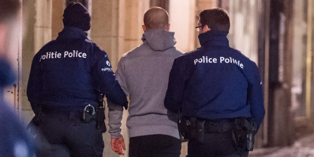 Police lead away a man during a raid in Brussels on Sunday, Nov. 22, 2015. Western leaders stepped up the rhetoric against the Islamic State group on Sunday as residents of the Belgian capital awoke to largely empty streets and the city entered its second day under the highest threat level. With a menace of Paris-style attacks against Brussels and a missing suspect in the deadly Nov. 13 attacks in France last spotted crossing into Belgium, the city kept subways and underground trams closed for a