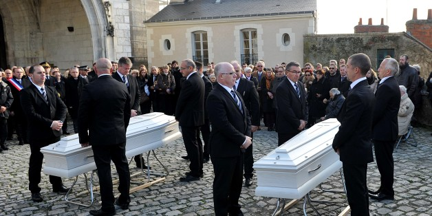 Friends and relatives of victims of the Paris terror attack claimed by the Islamic State group (IS) , Anna and Marion Petard-Lieffrig assemble before the coffins of the two sisters outside the the Saint Louis Cathedral in Blois, central France, on November 23, 2015 before the start of the funeral ceremonies.  Anna Petard, 26, and her sister Marion, 30, were killed in the restaurant 'Le petit Cambodge' during the coordinated terror attacks claimed by the Islamic State group (IS) in Paris on Novem