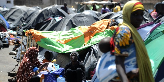 Illegal migrants from Niger sit next to their tents on May 14, 2014 after settling, some of them for more than one year, near the fruit market in the Algerian town of Boufarik, 35 km south of the capital Algiers in the Blida province. The Sahel-Sahara region has been plagued by jihadist violence and severe food shortages. Some Algerian newspapers articles have recently shown signs of racism against African migrants arriving in the country to flee violence and poverty back home.  AFP PHOTO/FAROUK BATICHE        (Photo credit should read FAROUK BATICHE/AFP/Getty Images)