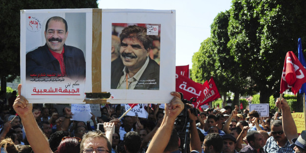 A Tunisian demonstrator holds a poster of slain politicians, lawyer and secular politician Chokri Belaid, left poster, and Mohamed Brahmi, during a march to protest a law offering amnesty for those accused of corruption, in Tunis, Tunisia, Saturday Sept. 12, 2015. The controversial draft law on economic reconciliation is a centerpiece of the new government's program and seeks to boost the economy by clearing cases against businessmen and civil servants accused of corruption. (AP Photo/Riadh Drid