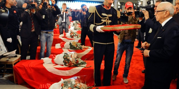 """Tunisia's President Beji Caid Essebsi, right, attends a funeral ceremony held at the Presidential Palace in Carthage near Tunis, Tunisia, to honor the members of the Republican Guard killed in Tuesday's bomb blast on a bus, Wednesday, Nov. 25, 2015. Tunisian authorities said Wednesday they have discovered a 13th body in the bus attacked in central Tunis. The body is believed to be the """"terrorist who caused the explosion,"""" the Interior Ministry said. (AP Photo/Hassene Dridi)"""