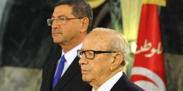 """Tunisian President Beji Caid Essebsi, front and new Prime Minister Habib Essid stand at attention during a cabinet takeover ceremony in Tunis, Friday, Feb. 6, 2015.  Prime Minister Essid, whose cabinet has ministers from four parties including the powerful Islamist group, promised """"work and nothing but work"""" on the country's economic and security problems.  (AP Photo/Hassene Dridi)"""
