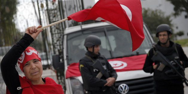 A woman waves the Tunisian flag as policemen stand guard at the National Bardo Museum two days after gunmen attacked the museum and killed scores of people in Tunis, Tunisia, Friday, March 20, 2015.  The Islamic State group issued a statement Thursday claiming responsibility for the deadly attack on Tunisia's national museum that killed scores of people, mostly tourists. (AP Photo/Christophe Ena)
