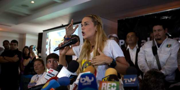 Lilian Tintori, center, wife of jailed opposition leader Leopoldo Lopez, speaks during a news conference in Caracas, Venezuela, Thursday, Nov. 26, 2015. An opposition leader was shot to death Wednesday while campaigning for next week's congressional elections in Venezuela, members of his political party said. The shooting took place in the central town of Altagracia de Orituco, said the leader of the Democratic Action Party, Carolos Prosperi. He said he heard gunshots as the rally was breaking u