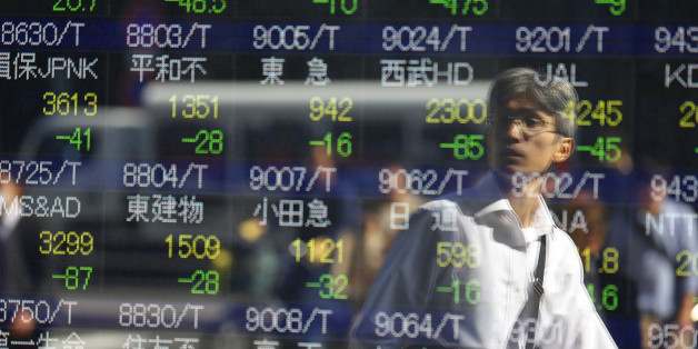 A man is reflected on an electronic stock indicator of a securities firm in Tokyo, Wednesday, Oct. 14, 2015.  Asian stock markets extended losses Wednesday following a drop on Wall Street as investors digested weak Chinese trade data and China's low inflation rate.(AP Photo/Shizuo Kambayashi)