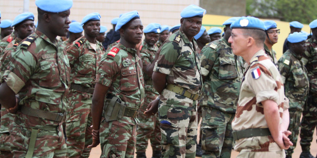 A French soldier stands alongside African troops who helped France take back Mali's north earlier this year, as they participate in a ceremony formally transforming the force into a United Nations peacekeeping mission, in Bamako, Mali, Monday, July 1, 2013. The roughly 6,000 African troops will be folded into the Integrated United Nations Mission for the Stabilization of Mali, or MINUSMA, which is expected to grow to more than 12,000 soldiers. (AP Photo/Harouna Traore)